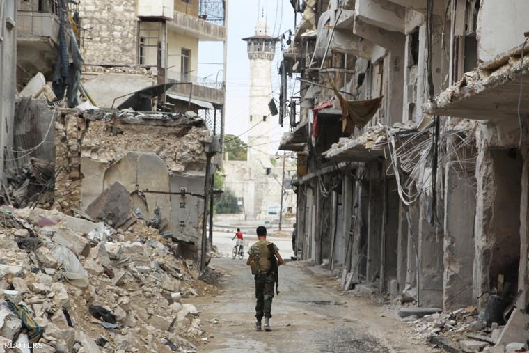 Egy katona sétálgat Aleppó romjai között
